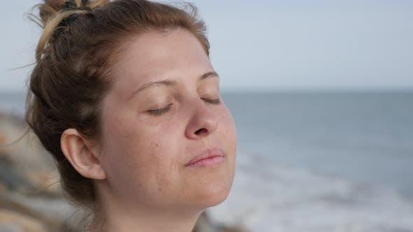 Thumbnail for Meditation of blonde Caucasian female on ocean beach 4K 2160p 30fps UltraHD footage - Blonde woman e