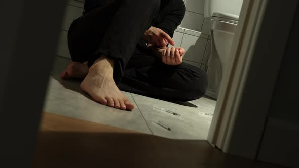 Thumbnail for Drug Addict Sits On Floor In Toilet And Takes Injection In His Hand