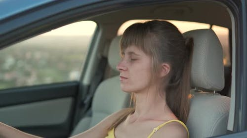 Young woman driver relaxing behind the wheel of her car.
