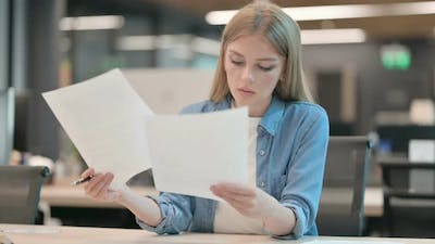 Young Woman Reading Documents in Office
