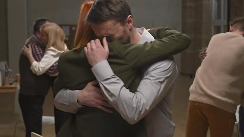 Crying Man Hugging His Partner at Psychotherapy Group Session