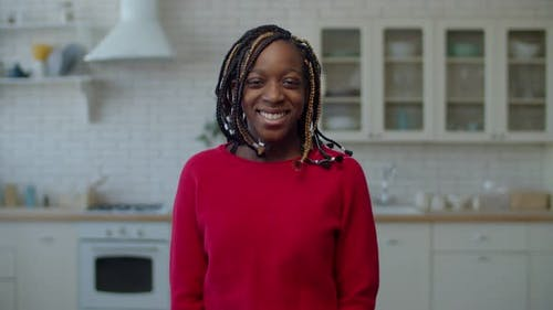 Cheerful Preadolescent Girl with Braids Smiling at Home