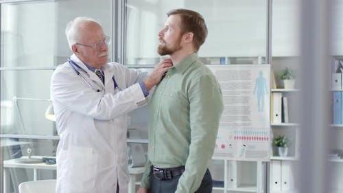 Senior Arzt untersucht Hals Lymphknoten des jungen Mannes