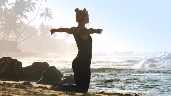 Thumbnail for Sporty Girl in Black Tracksuit Practices Yoga Pose Pigeon