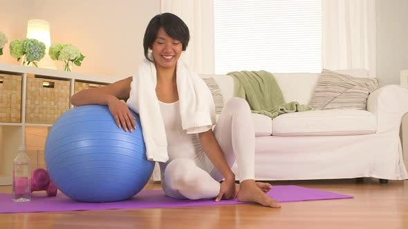 Taiwanese woman sitting on yoga mat in living room