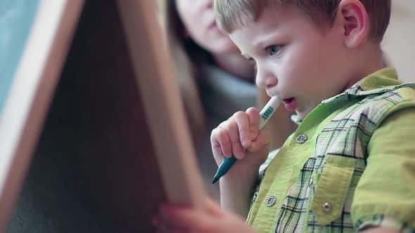 Mère dit à son fils qu'il a besoin d'écrire sur le tableau