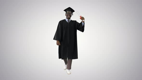 Happy African American Male Student in Graduation Robe Walking with Diploma and Talking To Camera on