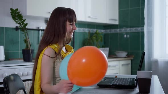 Thumbnail for Self-isolation, Beautiful Young Female with Balloons Looks at Camera on Laptop and Communicates with