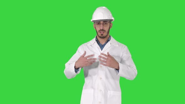 Thumbnail for Arab Engineer Presenting Something Talking To Camera While Walking on a Green Screen, Chroma Key