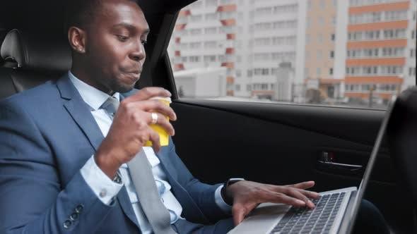 Afroamerikaner Geschäftsmann fährt mit Laptop im Auto