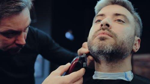 Adult Man Cuts His Beard in the Barbershop