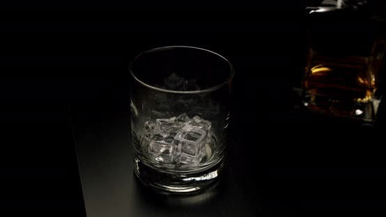 Thumbnail for Slow Motion Drops the Ice Into a Glass Later Golden Whiskey Pouring in the Glass with Ice Cubes From