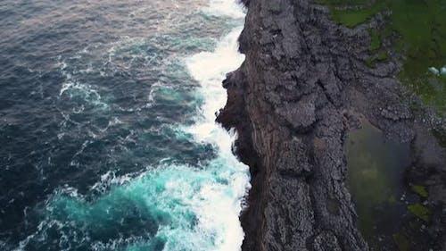 Aerial view of water encountering agitated Atlantic ocean, Faroe island.