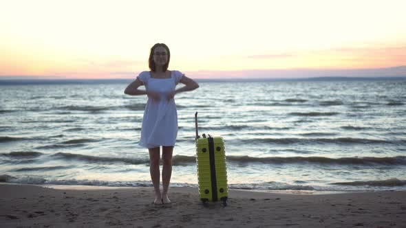 Thumbnail for Young Woman with a Yellow Suitcase on the Beach By the Sea. A Girl in a White Dress By the Sea at