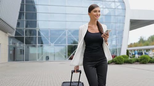 Business Trip. Beautiful Woman With Phone And Suitcase