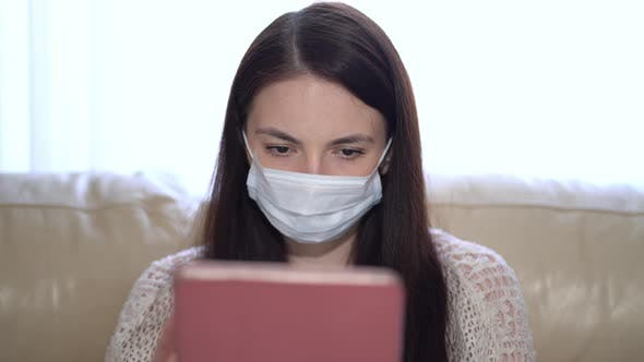 Thumbnail for Woman in a Medical Mask Uses a Tablet at Home During Quarantine