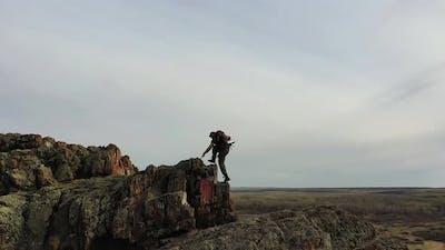 A Man Climbing to the Top of a Mountain