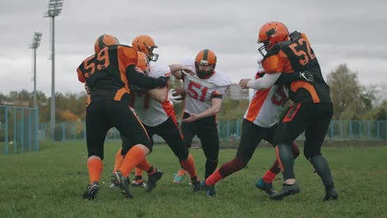 American Football Football Team in the Game Training Aggressive Opposition During the Game the Fight