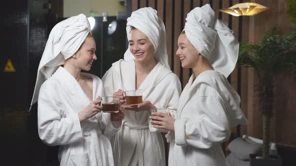 Three Girlfriends Drinking Herbal Tea After Spa Treatment Having Rest Enjoying Beauty Procedures