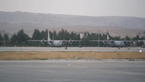 Large Airplanes Stand on Local Airport Airfield Against Hill