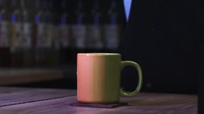 Throwing a Sugar Cube in a Cup of Coffee  Coffee Splashes on the Table