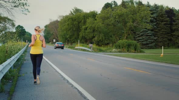 Cover Image for Middle-aged Woman Runs Along the Road in a Typical Suburb of the United States, a Healthy Lifestyle