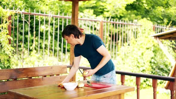 Man Is Standing in a Summer House, Cooking Pilaf, for a Picnic. He Cleans the Onion, on a Red