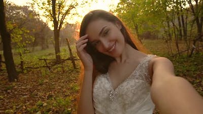 Point of View Shot of Attractive Bride Is Posing Into Camera Against Sunny Rays at Sunset with