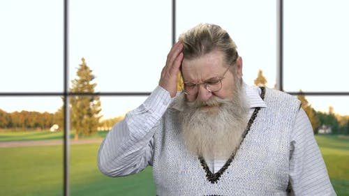 Unhappy Senior Man Suffering From Headache.