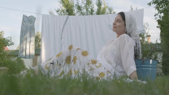 Thumbnail for Attractive Senior Woman with a White Shawl on Her Head Resting in the Garden Sitting on the Grass