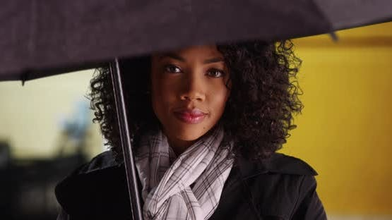 Close up of pretty black female shielding herself from rain with black umbrella