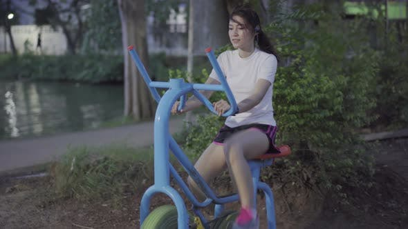 woman working out on the exercise bike in park