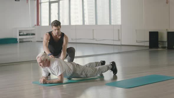 Thumbnail for Aged Man Training Plank Workout with Sport Coach in Fitness Club Together