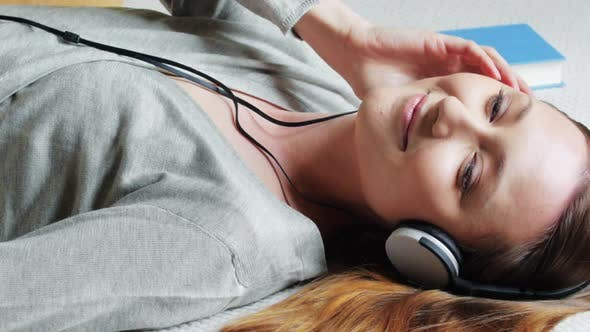 Thumbnail for Woman lying on bed listening to music