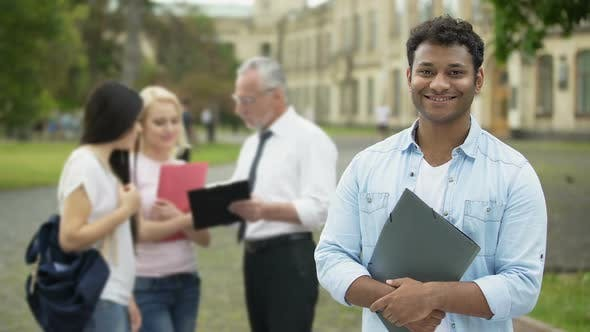 Thumbnail for Happy Hispanic Student Standing Near College and Looking Into Camera, Education