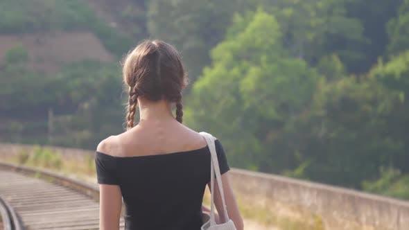 Thumbnail for Girl in Black Top Walks To Railway Among Nature Closeup