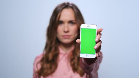 Thumbnail for Businesswoman Showing Smartphone with Green Screen in Studio