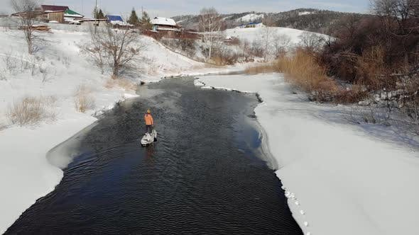 a Man with a Hat Paddling on a Paddle Board in Winter