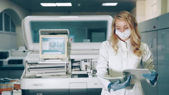 Portrait of a Lab Worker. Female Medic in Protective Medical Mask in Laboratory Browses Records in