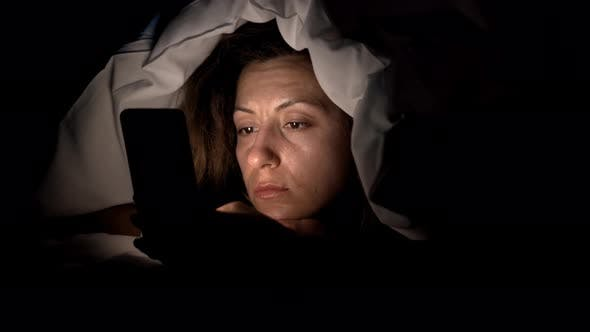 Thumbnail for Young Woman in Bed with Smartphone. Woman Starring at Cellphone Device Before Going To Bed