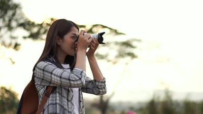 tourist woman taking a photo with her camera in nature