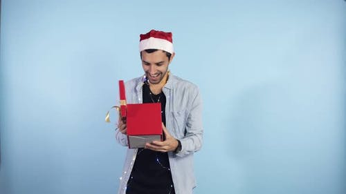 Positive Young Guy in Christmas Hat and Garland on Neck Recieves Surprise From From the Side Female