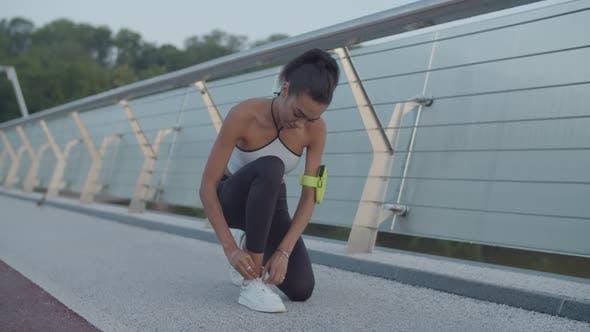 Athlete Woman Tying Running Shoes During Jog at Dawn