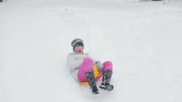 Kleinkind Mädchen gehen unten ein Schlitten auf ein schneebedeckter Hügel