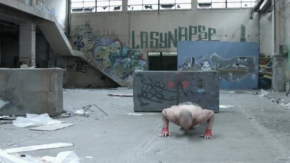 Thumbnail for A shirtless personal trainer man does clapping pushups inside an abandoned building
