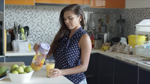 Charming Happy Woman Nippen frisch Orangensaft stehend in der Küche