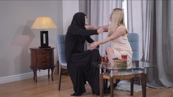 Thumbnail for Long Shot of Muslim and Caucasian Women Sitting at the Table at Home and Hugging. Best Friends From