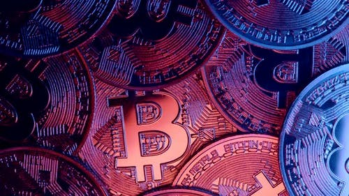 Closeup of Bitcoins Rotating Under Blue Light Neon Light