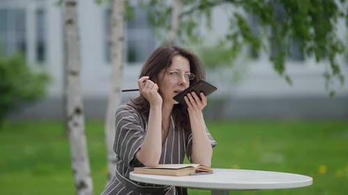 Female Student Searches for Information on the Subject with the Help of a Voice Assistant on the