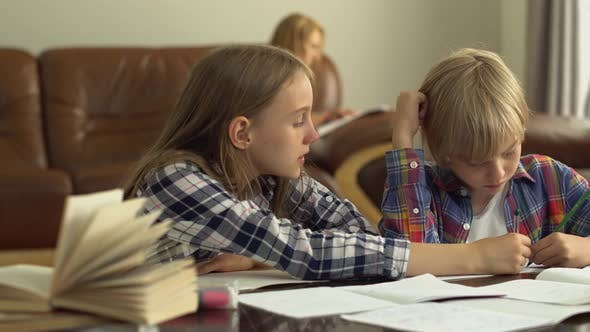 Thumbnail for Cute Little Boy and Girl Studying at Home in The Foreground While Their Mother Is Sitting in The Background